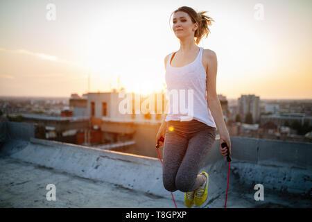 Portrait de jeune femme à monter sur le toit le saut à la corde. Femme Fitness faisant sauter à l'extérieur d'entraînement sur une journée ensoleillée. Banque D'Images