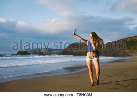Jeune Femme prenant une photo avec son smartphone selfies caméra sur les vacances d'été à la plage. La plage de Rodiles, Asturias, Espagne. Banque D'Images