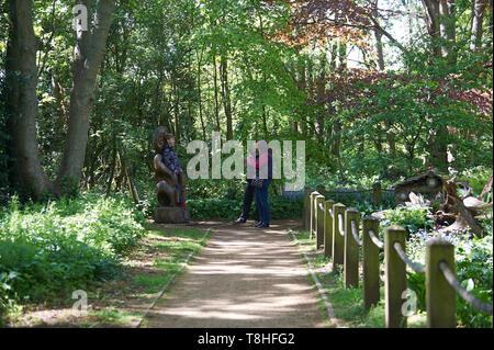 Mère et père de prendre des photographies d'enfant il y a sur une sculpture en bois dans la lumière d'un gris forestiers à feuilles larges et au printemps, UK, FR. Banque D'Images