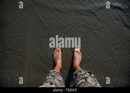 Les pieds de l'homme debout sur beach, Ao Nang, Krabi, Thaïlande
