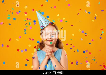 Cute little girl célèbre l'anniversaire. L'enfant ferma les yeux et fait un souhait dans la pluie de confettis. Closeup portrait sur fond jaune. Banque D'Images