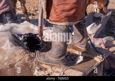 La Mongolie, à l'Est de la Mongolie, steppe mongole, bergers en vêtements traditionnels pour sortir de l'eau de puits dans le milieu de l'hiver pour donner les chevaux un verre Banque D'Images