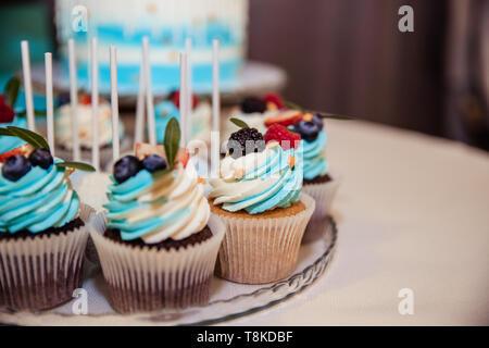 De délicieux petits gâteaux aux fruits rouges cupcakes colorés.avec le buttercream et les framboises, bleuets.Maison de vacances spécial événement célébration.Kids party Banque D'Images