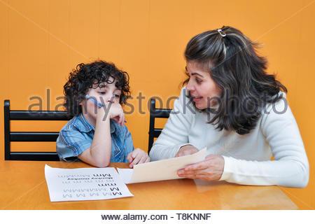 Les photos de famille: Maman enseigne la lecture d'un petit garçon assis sur une chaise à la table sur fond orange Banque D'Images