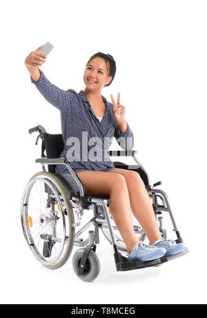 Asian Woman in wheelchair selfies prenant sur fond blanc Banque D'Images