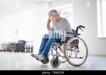 Déprimé senior man in wheelchair at home Banque D'Images