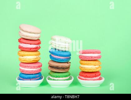 Macaron cookies dans de petits plats blanc empilés dans des lignes graduées, la pâtisserie française traditionnels colorés sur un fond vert menthe. Banque D'Images