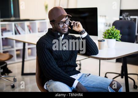 Businessman talking on smartphone et travaillant en bureau. African Male assis à son lieu de travail.