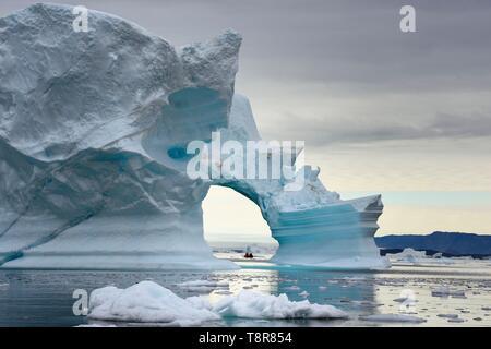 Le Groenland, côte nord-ouest, la mer de Baffin, Fjord d'Inglefield vers Qaanaaq, iceberg formant un arc et une exploration PolarCirkel bateau (Zodiac) du MS Fram navire Hurtigruten de cruse Banque D'Images
