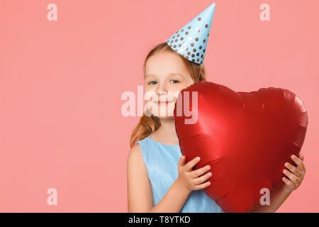 Happy little girl dans un bouchon est titulaire d'un gros ballon en forme de coeur. Portrait d'un bébé sur un fond rose. Copier l'espace. Banque D'Images