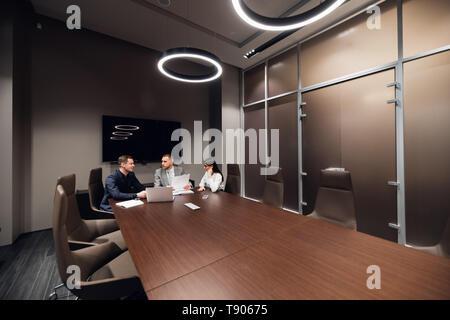 Les collègues réunis à la salle de conférence pour discuter du projet in office