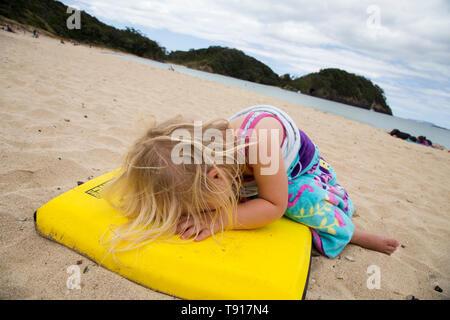 Fille de l'école avant d'avoir un réacteur à la plage parce qu'elle ne veut pas aller à la maison. Belle journée, le sable blanc, la mer bleu clair. Girl conseil jaune Banque D'Images
