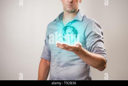 Casualy habillé businessman holding projections virtuelles du monde dans sa main