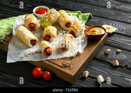 Planche de bois avec de délicieux petits pains à saucisse et sauces sur table en bois Banque D'Images