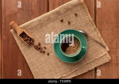 Une tasse de café noir avec des grains de café torréfiés, tourné par le haut sur un fond de bois rustique foncé avec une place pour le texte Banque D'Images