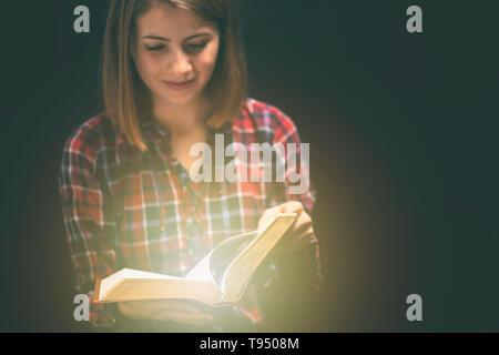 Jeune femme readin bible dans une pièce sombre Banque D'Images
