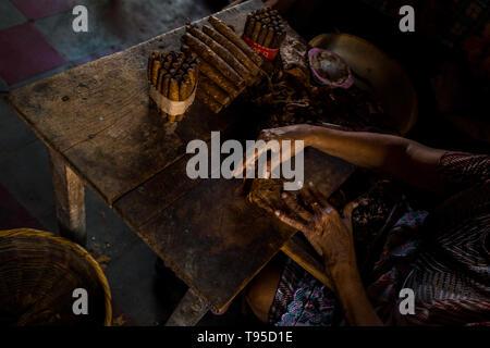 Laura Peña, un 67-ans femme salvadorienne, rouleaux de feuilles de tabac dans un cigare à la main dans sa maison de Suchitoto, El Salvador. Banque D'Images