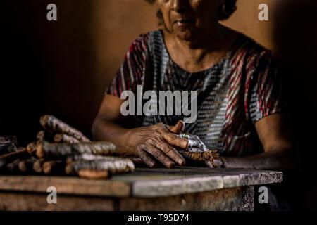Laura Peña, un 67-ans femme salvadorienne, rouleaux de feuilles de tabac pour faire des cigares faits à la main dans sa maison de Suchitoto, El Salvador. Banque D'Images