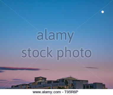 Leith Docks, Edinburgh, Ecosse, Royaume-Uni, 16 mai 2019. Météo France: un ciel clair coloré crépuscule sur le port de Leith avec une presque pleine lune brillante sur Victoria Quay, édifice du gouvernement écossais Banque D'Images