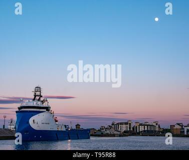 Leith Docks, Edinburgh, Ecosse, Royaume-Uni, 16 mai 2019. Météo France: un ciel clair coloré crépuscule sur le port de Leith avec un navire d'approvisionnement à l'étranger appelé NAO Fighter dans le port illuminé par les derniers rayons du soleil avec une presque pleine lune brillante dans le ciel bleu Banque D'Images