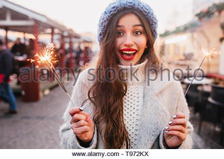 Blissful brown-haired woman avec sourire sincère profitant des vacances de Noël et posing with sparkler. Fille charmante en soft blue hat holding Bengal la lumière sur la rue. Banque D'Images