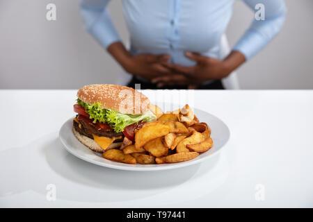 Jeune femme souffrant de douleurs à l'estomac pendant le petit-déjeuner