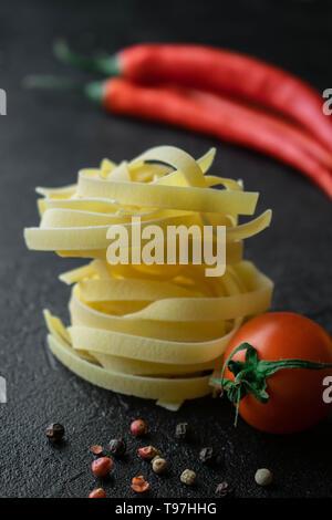 Sur fond noir boules de pâtes fettuccine brut avec tomates fraîches avec des racines, de poivre noir et rouge et deux gousses de chili Banque D'Images