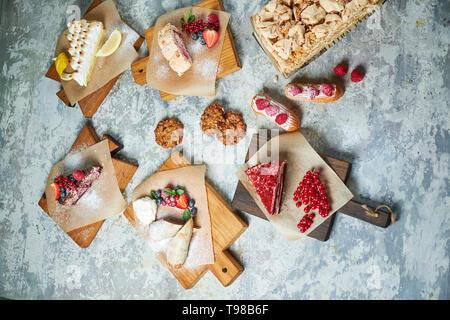 Assortiment de desserts sucrés: gâteaux, churos, rouleau de meringue, crème glacée, décorées avec des baies sur les planches de bois. Vue d'en haut. Fond texturé gris. Beaux plats de service. Le Dessert. La chaîne alimentaire Banque D'Images