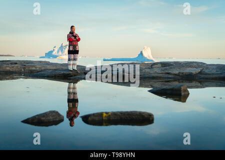 Femme Inuit en vêtements traditionnels se dresse sur la rive de la baie de Disko au Groenland, au milieu de l'été