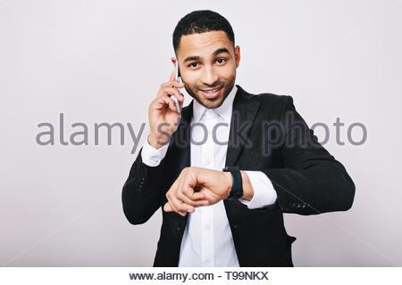 Portrait élégant élégant jeune homme en chemise blanche et veste noire parlant au téléphone, montrant watch et souriant à l'appareil photo sur fond blanc. Homme d'affaires, travail, réunion, l'humeur joyeuse, smiling, idée Banque D'Images