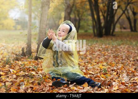 Cute little boy in raincoat having fun in autumn park Banque D'Images