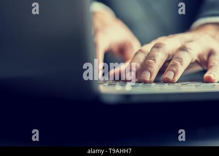 Portrait de l'arrière de l'ordinateur d'un businessman listening to dans une image aux couleurs rétro vintage. Banque D'Images