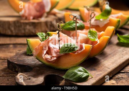 Des tranches de melon au jambon et feuilles de basilic, servi sur une planche en bois close up