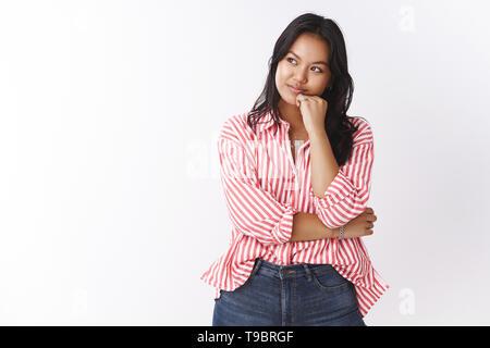 Hmm semble intéressant. Portrait d'intrigué et curieux séduisant jeune femme d'origine asiatique avec tatouage en Chemisier rayé la rêverie, s'appuyant sur bras Banque D'Images