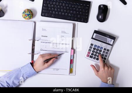 Un Portrait Of Businessman's Hand Using Calculator lors du calcul de facture sur 24 Banque D'Images