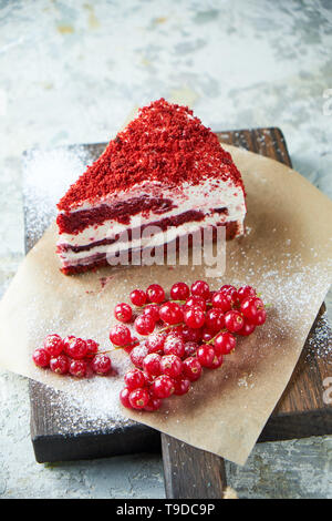 Gâteau de velours rouge et un tas de groseilles rouges sur une planche de bois. Fond texturé gris. Le Dessert. La chaîne alimentaire Banque D'Images