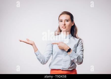 Jeune brunette business woman avec sourire et joie présente le produit, montre sa main de l'espace vide, copy space Banque D'Images