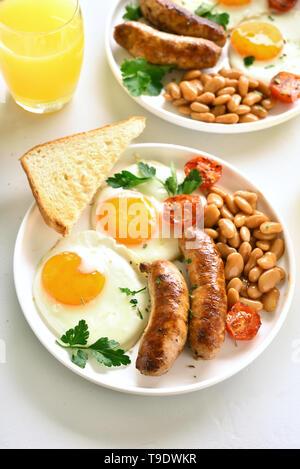 Le petit déjeuner anglais avec les œufs, saucisses, tomates, haricots verts, sur plaque sur table en pierre blanche Banque D'Images
