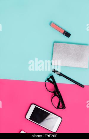 Matériel de bureau femmes et rose sur fond bleu. Mise à plat, vue du dessus. Le minimalisme Banque D'Images