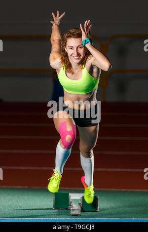 À partir de l'athlète féminine de la course sprint à partir de blocs en cours d'exécution sur un fond sombre Banque D'Images