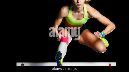 Jeunes femmes athlètes sautant obstacle au sprint. Sprinter sautant obstacle isolé sur fond noir Banque D'Images