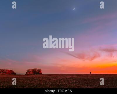 Vue imprenable de rocky sunset beach avec Lune se levant au-dessus de l'Océan Pacifique Banque D'Images