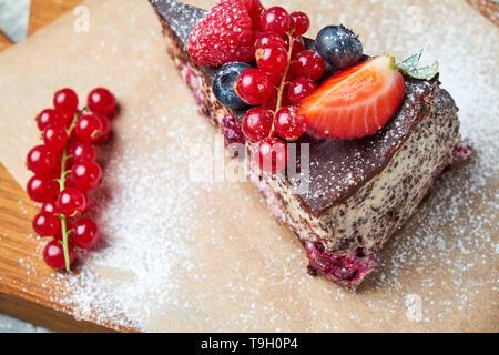 Piqûres d'un ivrogne cherry berry gâteau décoré avec des baies sur une planche de bois. Fond texturé gris. Beaux plats de service. Le Dessert. La chaîne alimentaire Banque D'Images