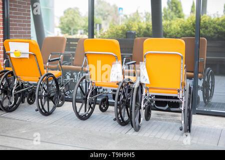 Groupe de vide et la couleur orange fauteuil roulant en face d'une fenêtre de l'hôpital. Banque D'Images