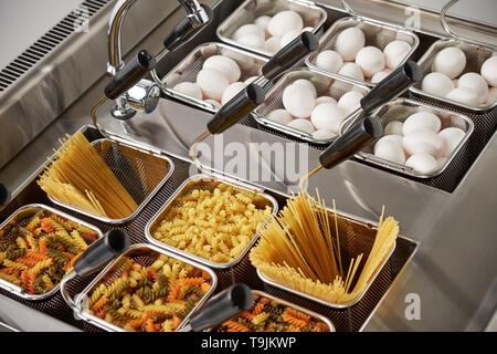 Cuisinière électrique à vapeur pour le deuxième cours. Corbeilles filet sont remplis avec des pâtes. L'équipement industriel cuisine alimentaires courants. Banque D'Images