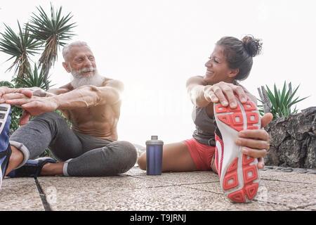Heureux amis remise en forme des exercices d'étirement des jambes ensemble dans la zone de plein air - couple sportive intense tout en riant à chaque autre