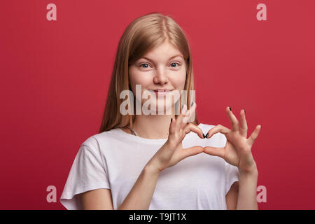 Amorous belle cheerful girl montrant coeur geste avec les mains si isolés sur fond rouge. portrait. I love u.Vous êtes dans mon coeur Banque D'Images