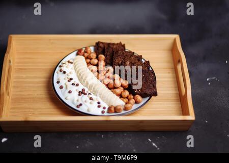 Gros plan du petit déjeuner sain plaque avec du yaourt au chocolat, banane, pain de seigle et de noisette sur la table de cuisine Banque D'Images