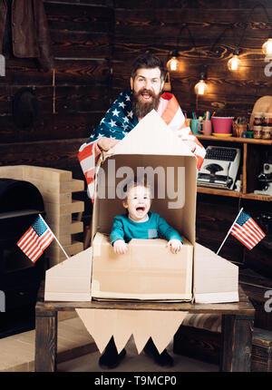Le père et le petit garçon en fusée en papier avec le drapeau américain. Le père et le petit garçon le jour de l'indépendance maison de vacances. Banque D'Images