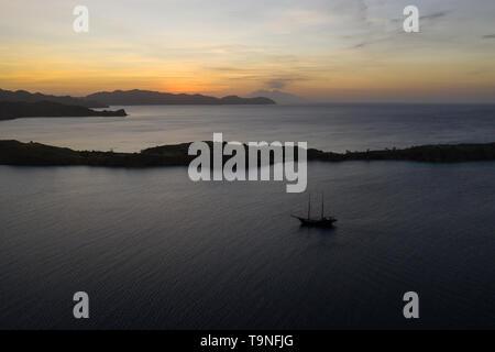 Un traditionnel Pinisi goélette navigue au coucher du soleil dans le Parc National de Komodo, en Indonésie. Cette zone tropicale est connu pour sa biodiversité marine. Banque D'Images